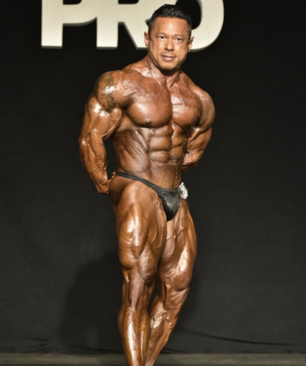 Leonardo Pacheco on the bodybuilding stage, showing his ripped obliques, chest, legs, and triceps from the side