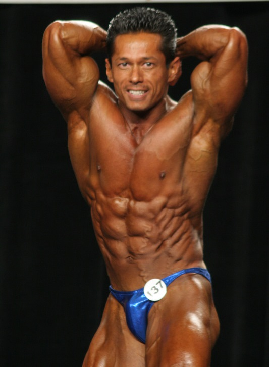 Leonardo Pacheco during his younger days in bodybuilding, flexing his abs on the stage
