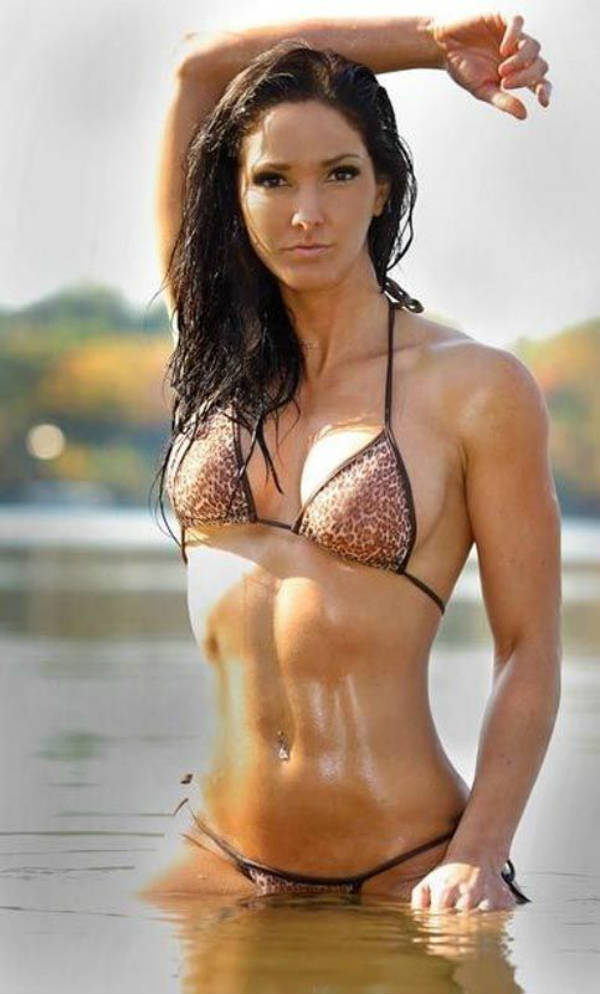 Lori Harder standing in a lake, showing off her toned abs and arms