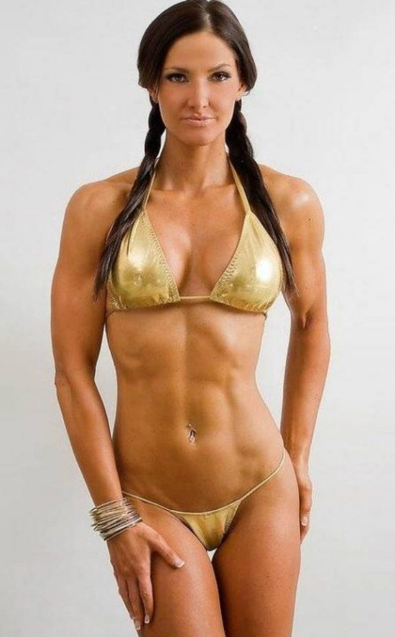 Lori Harder wearing a gold bikini looking lean and muscular