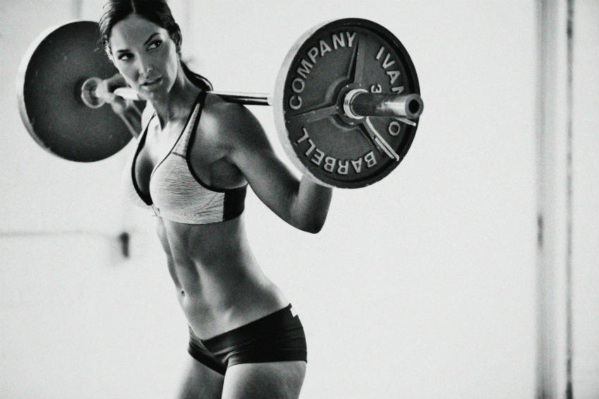 Lori Harder standing holding a barbell over her head