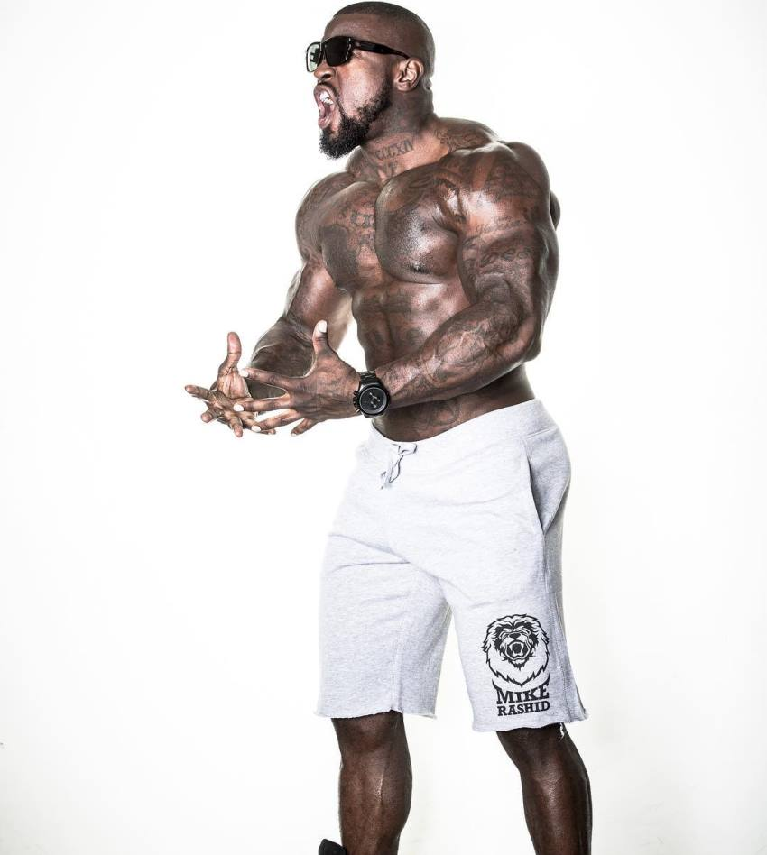 Mike Rashid wearing black sunglasses, being shirtless in white shorts, yelling at something and flexing his muscular body