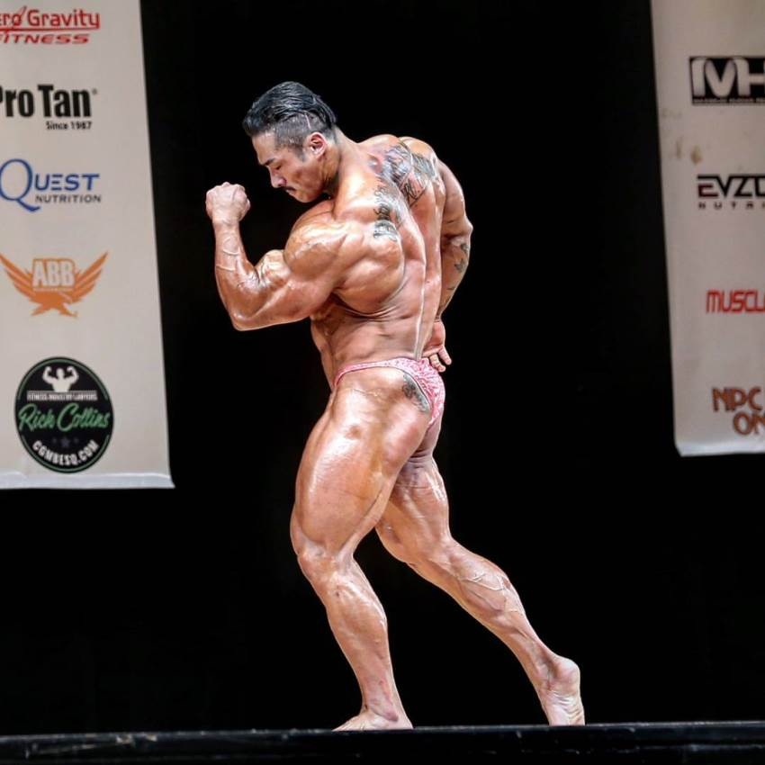 Nam Eun Cho posing on the bodybuilding stage, his back and legs looking massive