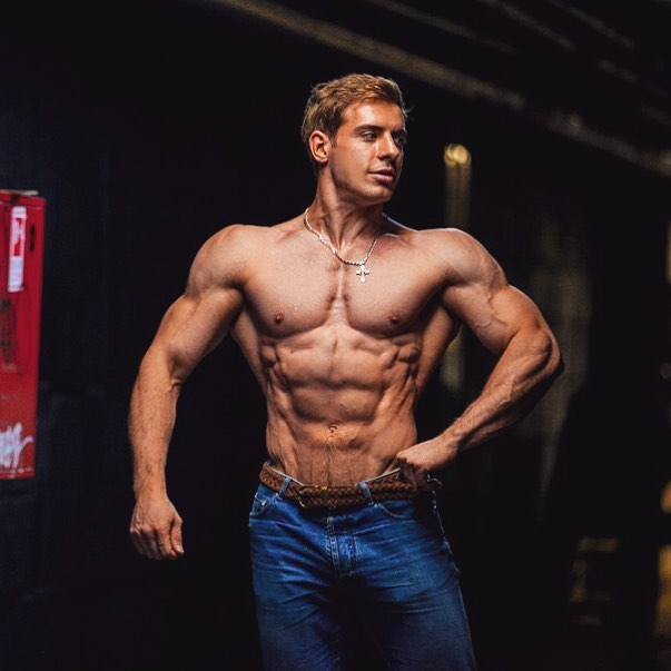 Nikolay Kuleshov standing shirtless in jeans, posing and showing his ripped and muscular body