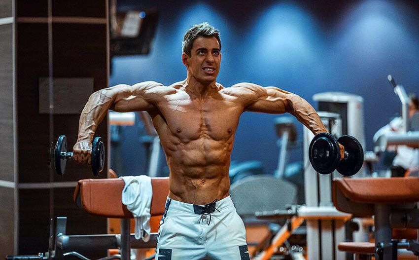 Nikolay Kuleshov training his side delts with dumbbells, being shirtless, looking ripped and muscular