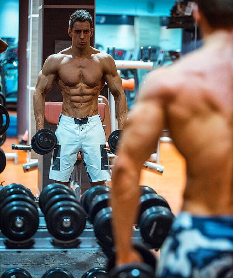 Nikolay Kuleshov standing by the gym mirror, looking at his ripped body as he performs an exercise with dumbbells