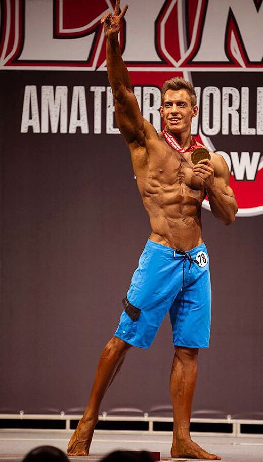 Nikolay Kuleshov standing on the Amateur Olympia stage, holding his medal in one hand, and waving to the audience with the other one