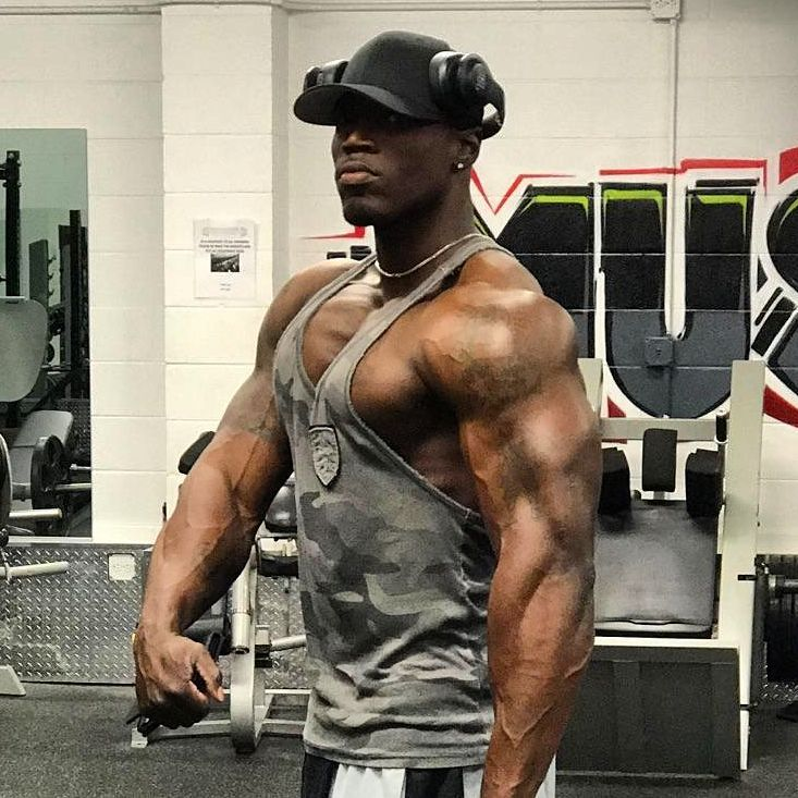 Otto Montgomery flexing his big and ripped arms in grey tank top
