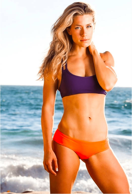 Rachel Elizabeth Murray standing on the beach, showing her toned abs