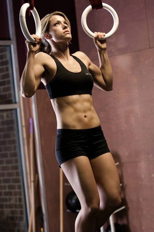 Rachel Elizabeth Murray hanging from two rings ,showing her core strength, toned abs and arms