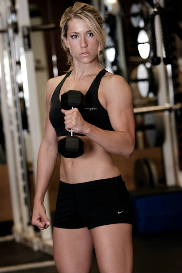 Rachel Elizabeth Murray lifiting small dumbbell, showing her toned arms, abs and legs