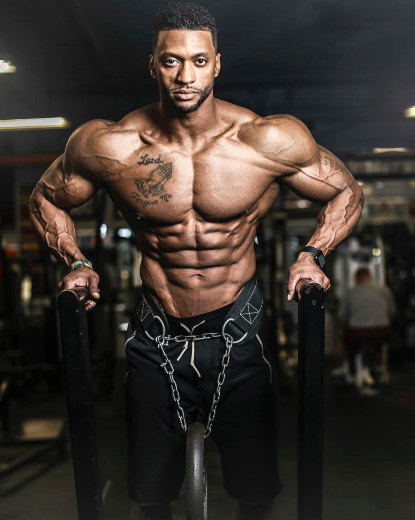 Shirtless Raymont Edmonds doing dips as he looks straight into the camera