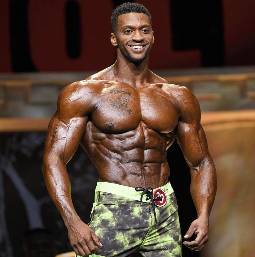Raymont Edmonds smiling at the audience, as he shows his oiled up, tanned up, and ripped physique