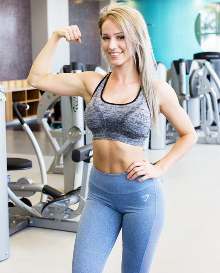 Robin Gallant tensing her biceps and abs for a photo