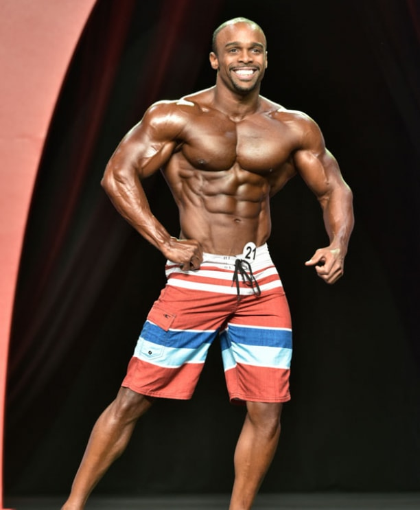 Ryan Hinton posing on the Mr. Olympia stage, smiling at the audience, and showing his lean physique