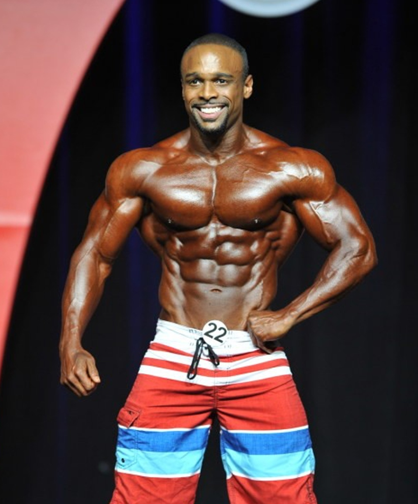 Ryan Hinton posing on the Mr. Olympia stage in red and blue shorts, displaying his ripped and muscular physique from the front