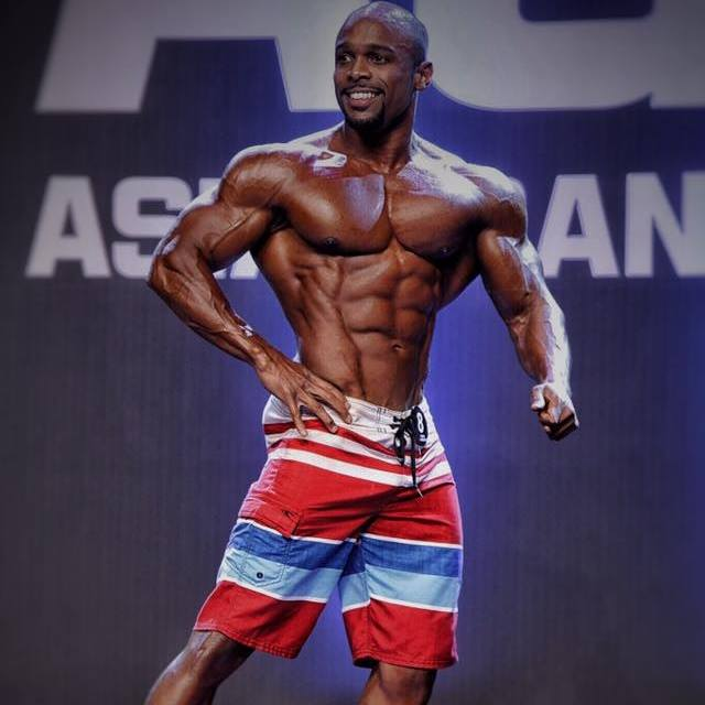 Ryan Hinton posing on the stage, showing his physique from the side, his abs, arms, and chest looking contest-ready