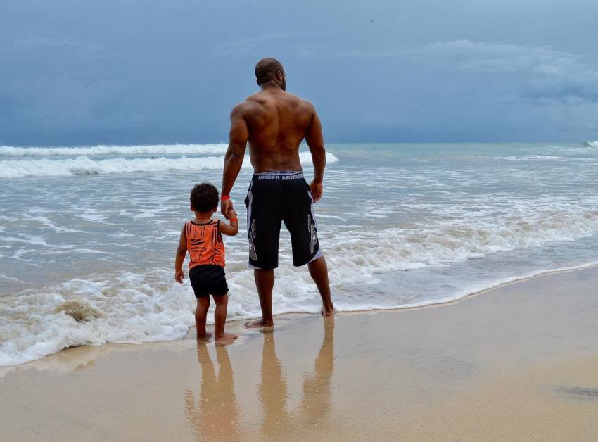 Ryan Hinton on a beach with his son on the left, Ryan's back and arms looking big and aesthetic