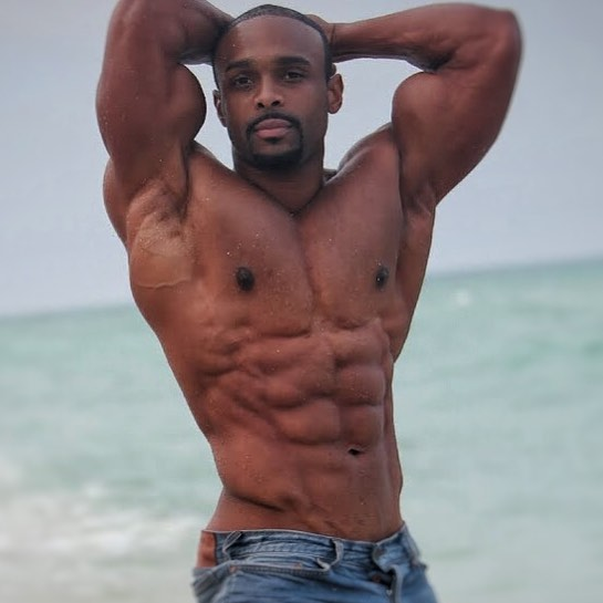Ryan Hinton flexing his abs for a photoshoot, looking lean and fit