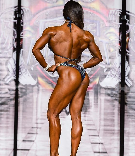 Sandra Grajales posing on a figure stage, her back looking aesthetic and ripped