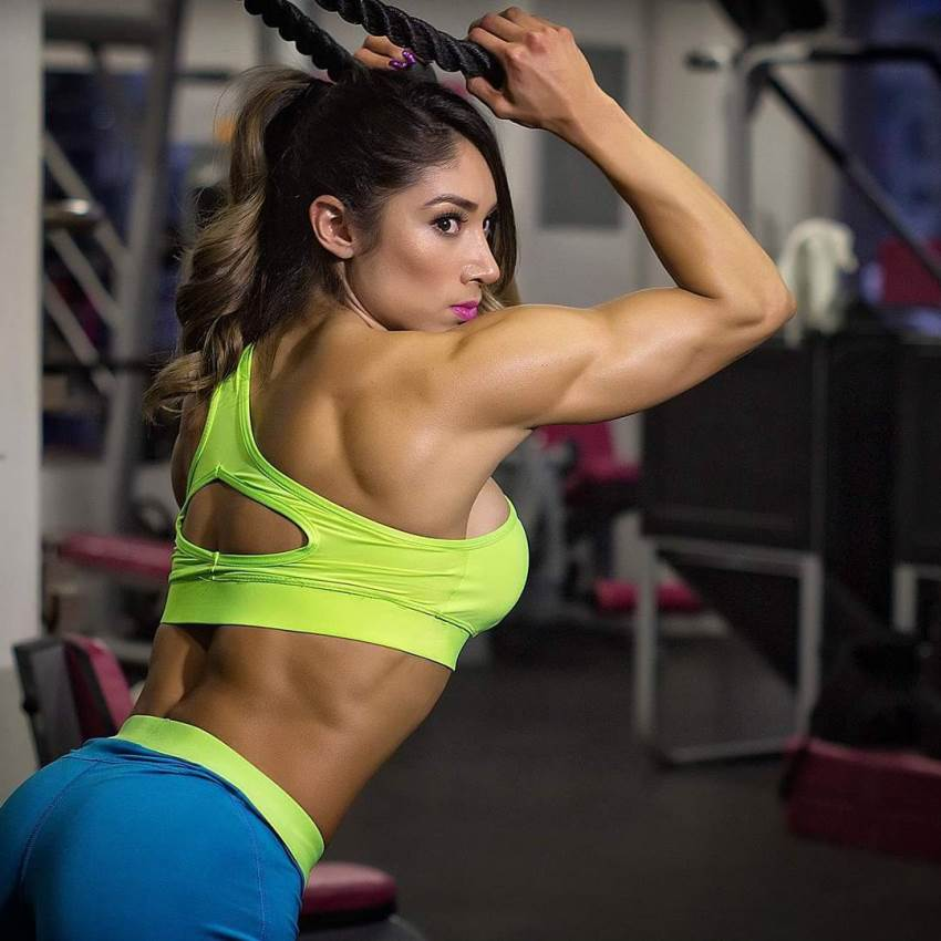 Sandra Grajales doing rope triceps extensions in the gym, leaning forward, her arms, shoulders, and lower back looking ripped and strong