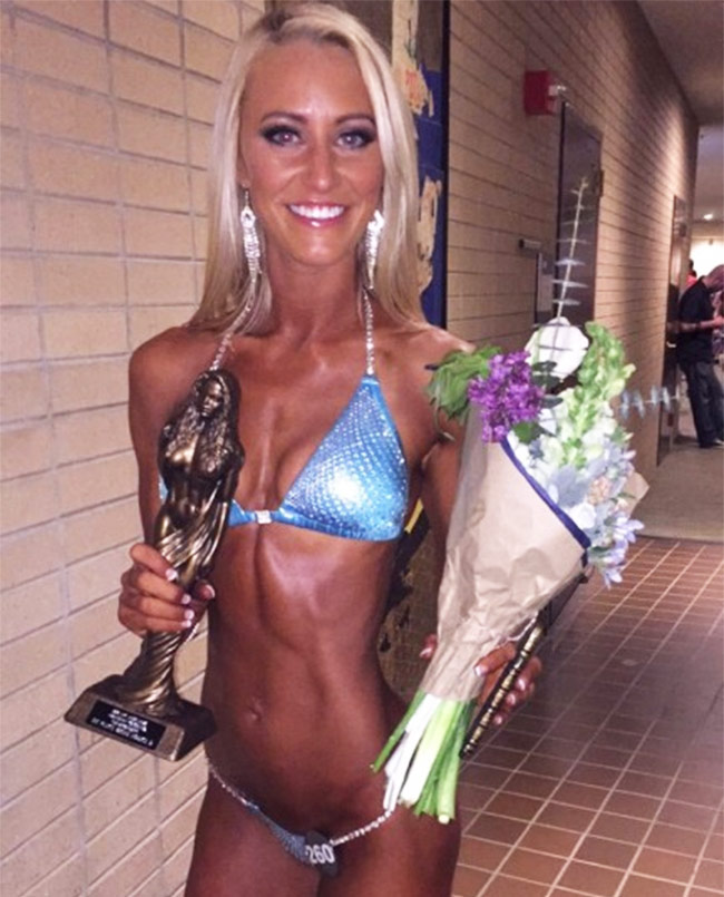 Shannon Henry in a bikini holding her first place trophy and flowers