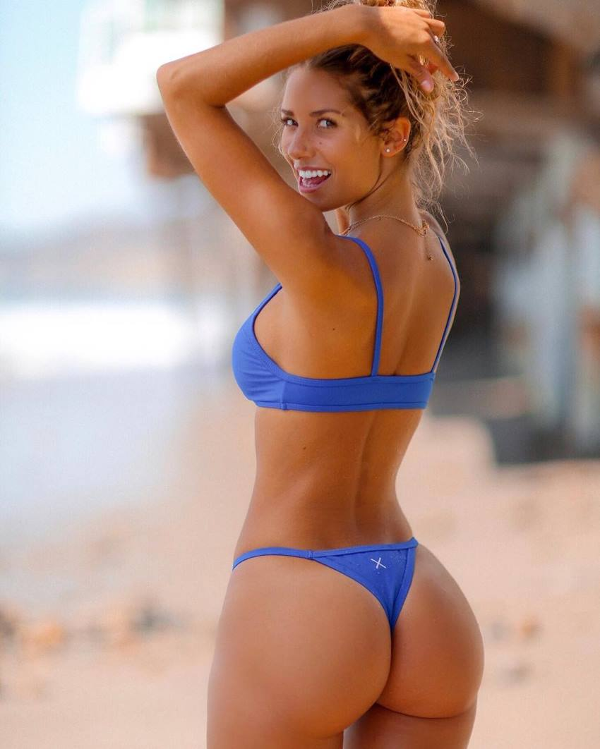 Sierra Skye in a blue swimsuit with her back turned, smiling at the camera and showing her incredible glutes
