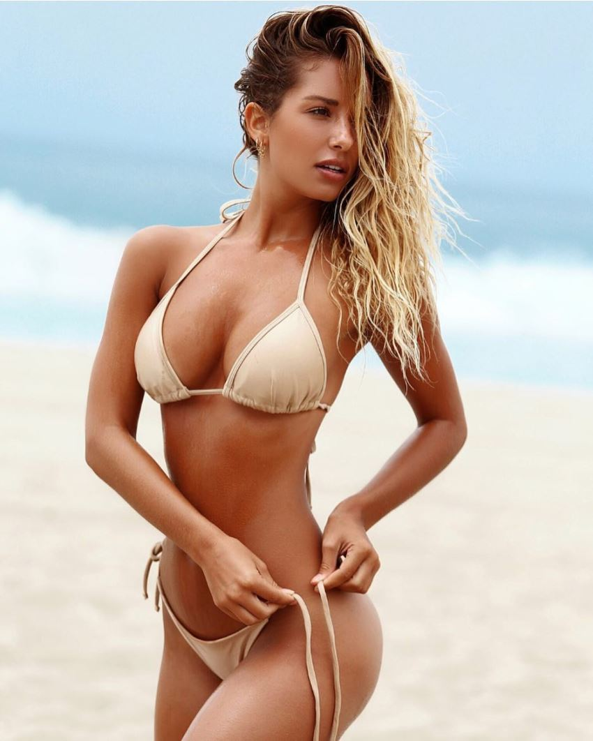 Sierra Skye tying her bikini panties on the beach, looking fit and healthy