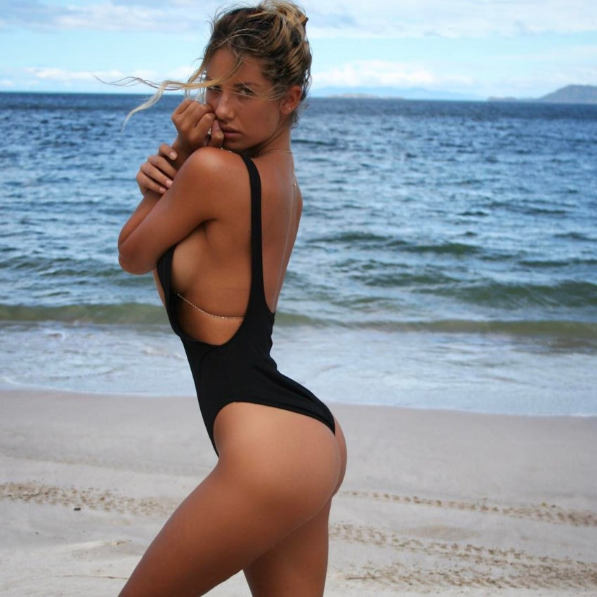 Side shot of Sierra Skye standing on the beach in her black swimsuit, her legs and glutes looking awesome