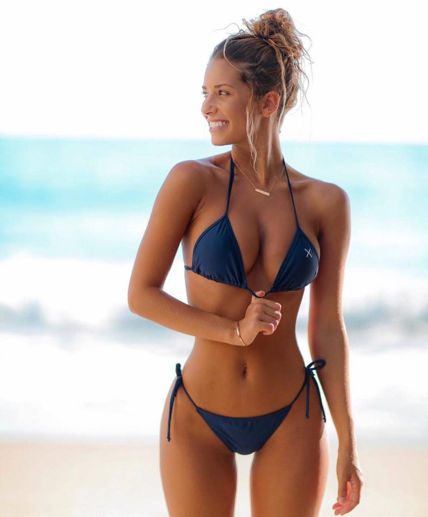 Sierra Skye in a blue bikini on the beach, looking at her right side and smiling, her figure looking incredible