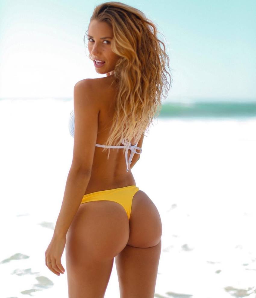 Sierra Skye in a yellow bikini on the beach, looking at the camera and showing her awesome glutes