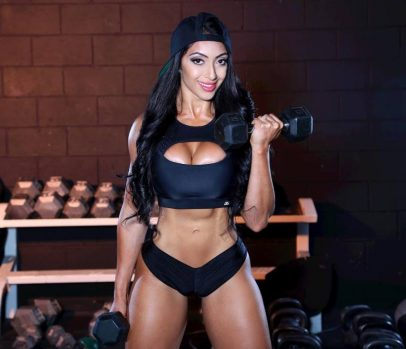 Sumeet Sahni doing biceps curls with dumbbels as she smiles at the camera, and flexes her toned abs