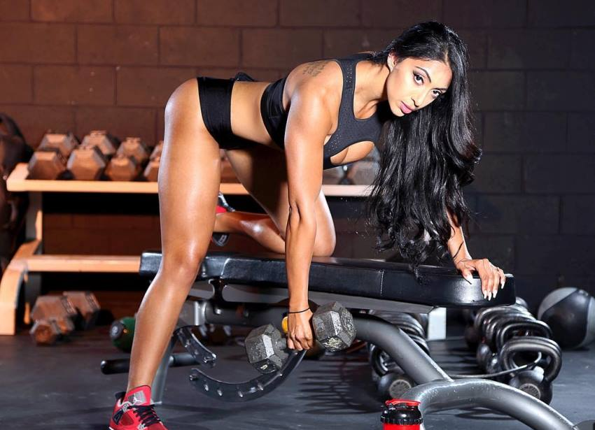 Sumeet Sahni doing one arm dumbbell rows, looking at the camera, and showing her toned legs and arms