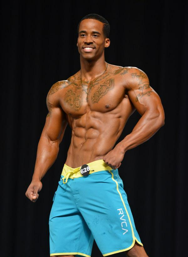Andre Smith posing on the stage in light blue trunks, smiling at the audience, looking ripped