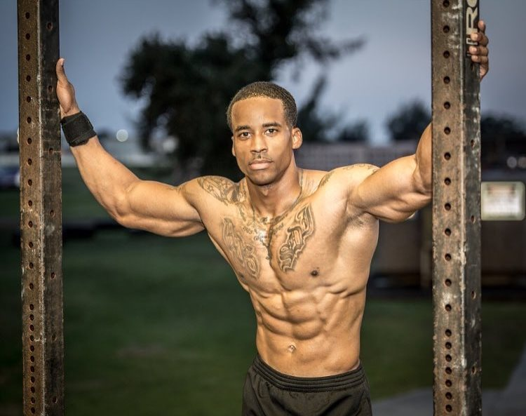 Andre Smith holding onto two iron bars, being shirtless, looking at the camera
