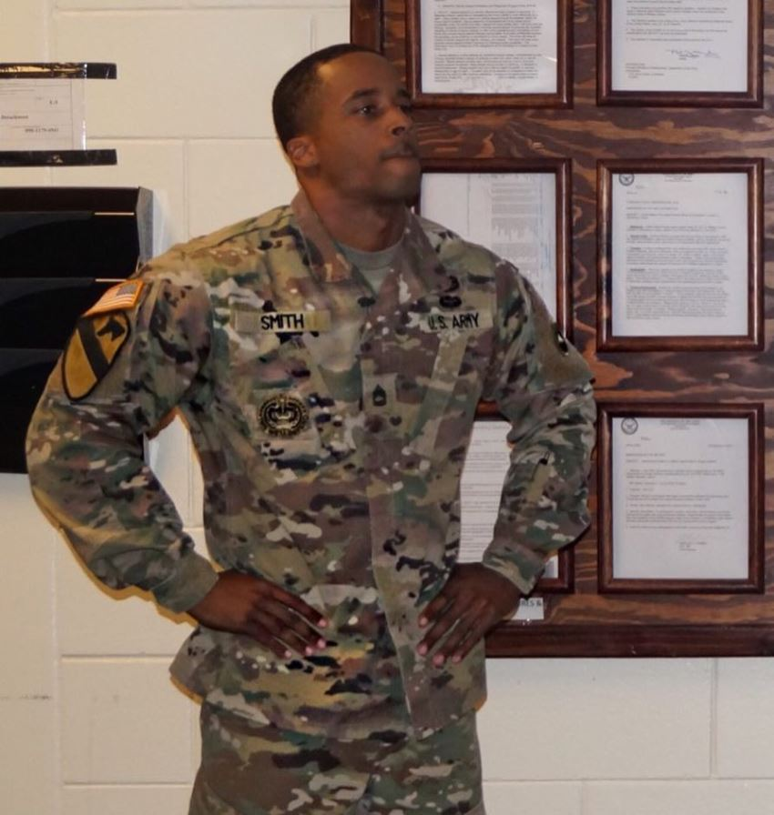 Andre Smith in his military suit, looking at something with a serious expression on his face