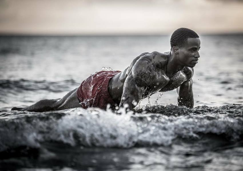 Andre Smith doing push ups on the shore, water splashing all over his ripped body