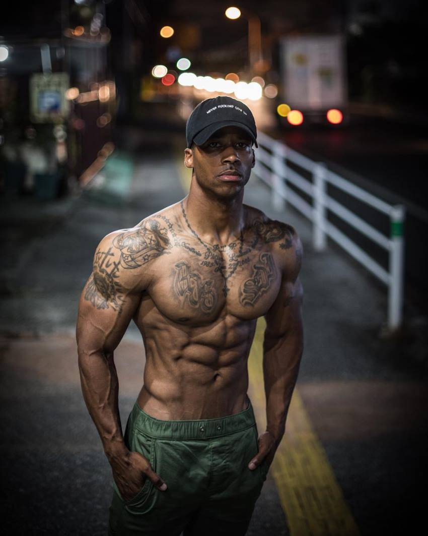 Andre Smith standing shirtless on the sidewalk, looking lean and muscular