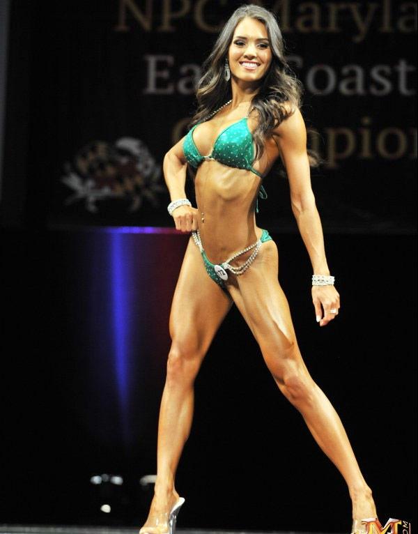 Ashley Flores posing on stage as a bikini athlete