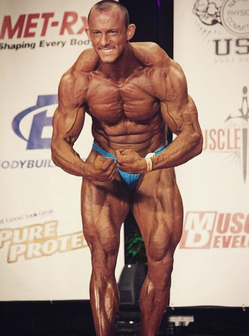 Brandon Gerdes performing a most muscular pose on the stage