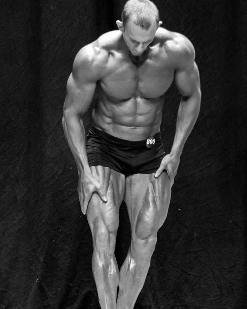 Brandon Gerdes flexing his legs and abs on the stage, looking down