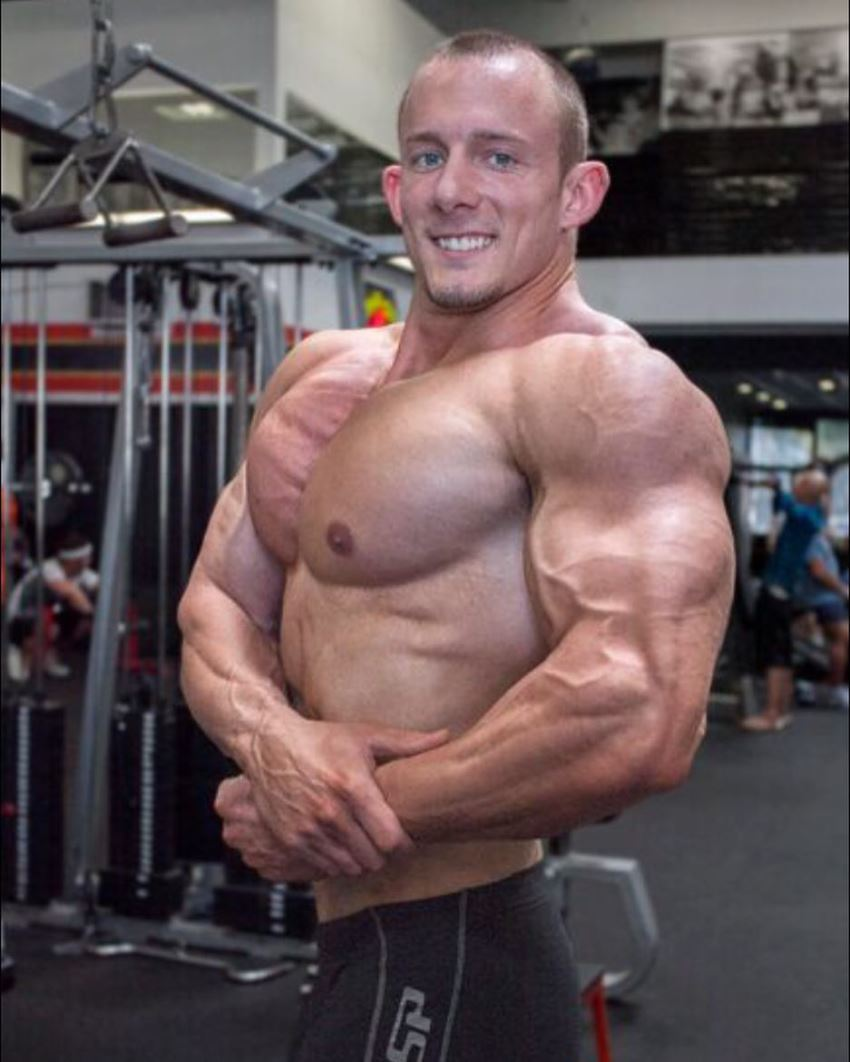 Brandon Gerdes doing a shirtless side chest pose in the gym