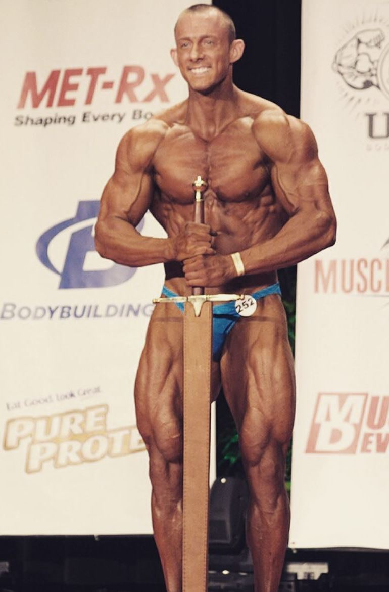 Brandon Gerdes posing with a sword on the stage