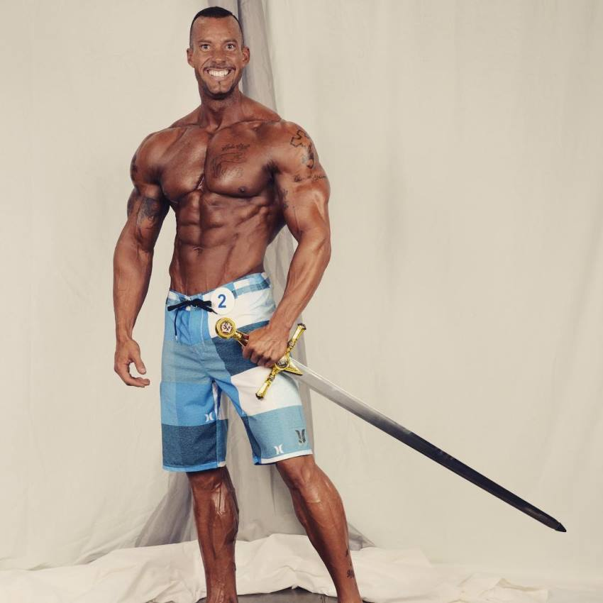 Brian Barthule posing with a sword after winning a contest, looking lean and aesthetic