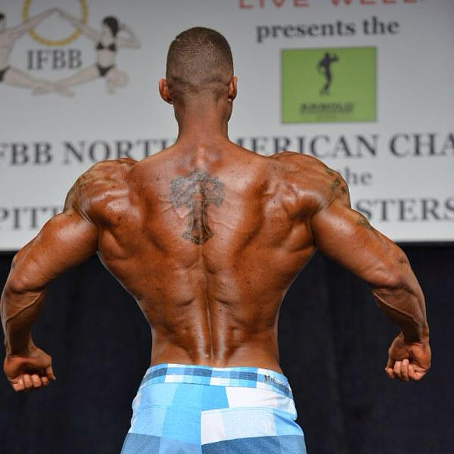Brian Barthule showcasting his ripped back to the judges on the stage