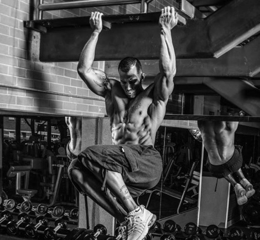 Brian Barthule performing hanging leg raises in the gym while displaying his awesome abs