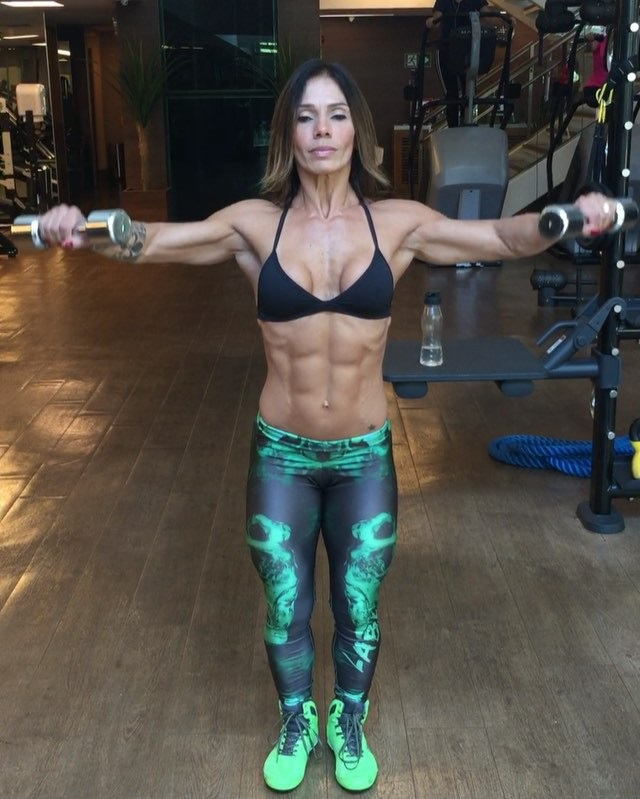 Cláudia Bonavoglia in the gym performing side lateral dumbbell raises