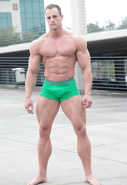Coty Reutzel standing in green underwear, looking big and ripped