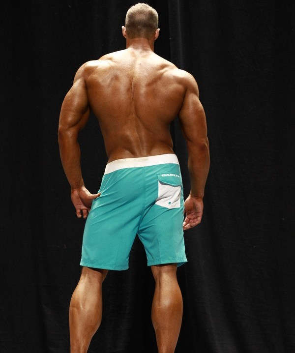 Coty Reutzel showing his back muscles to the judges on the bodybuilding stage