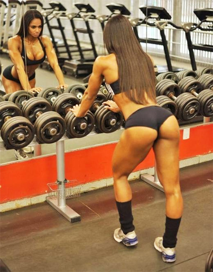 Denise Rodrigues leaning against a weight rack